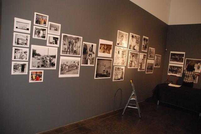 Laurie Steelink of Track 16 hangs the prints